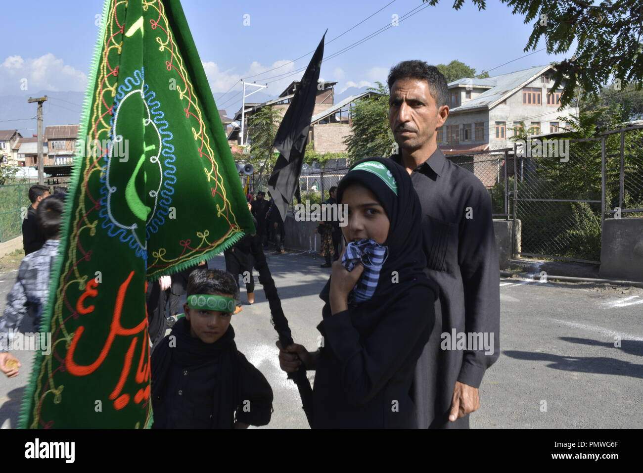 Kashmir Shiite Muslims girl seen holding a flag during the seventh day of Ashura. Ashura marks the martyrdom anniversary of the Prophet Muhammed's grandson the revered Imam Hussein who was killed in Karbala, Iraq in 680 AD in southern Iraq in the seventh century. - Stock Image