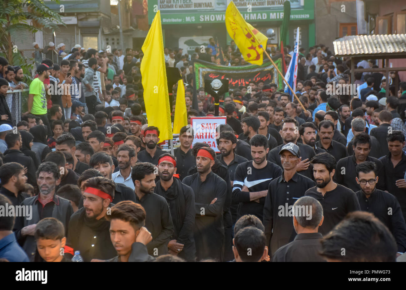 Kashmiri Shia Muslims seen performing rituals with flags during the procession. 7th day of Ashura procession which marks the martyrdom anniversary of the Prophet Muhammed's grandson the revered Imam Hussein who was killed in Karbala, Iraq in 680 AD in southern Iraq in the seventh century. - Stock Image