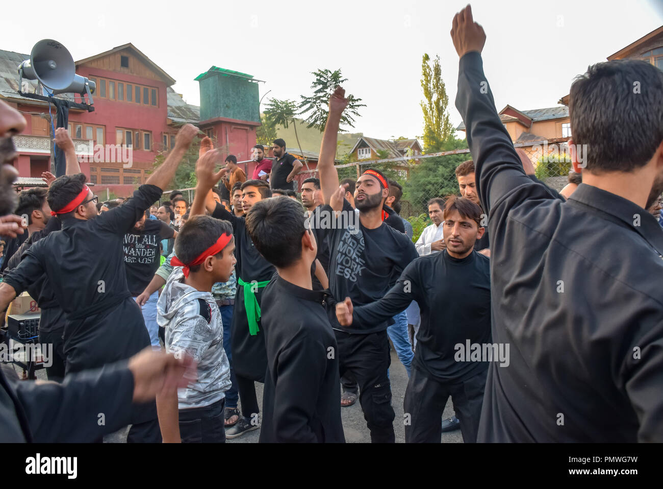 Kashmiri Shia Muslims seen raising their hands during the procession. 7th day of Ashura procession which marks the martyrdom anniversary of the Prophet Muhammed's grandson the revered Imam Hussein who was killed in Karbala, Iraq in 680 AD in southern Iraq in the seventh century. - Stock Image