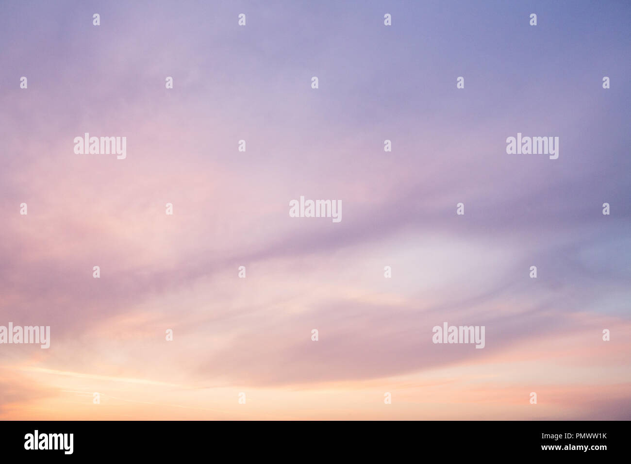 Soft hazy (blurry) clouds at sunset with pastel colours (colours) of yellows,  oranges, pinks, blues, and purples. The clouds fill the frame - Stock Image