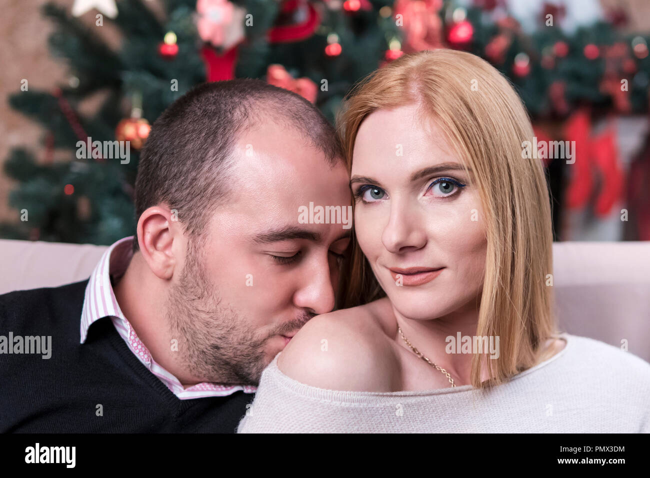 Man kisses a woman in a bare shoulder against the background of a Christmas tree - Stock Image