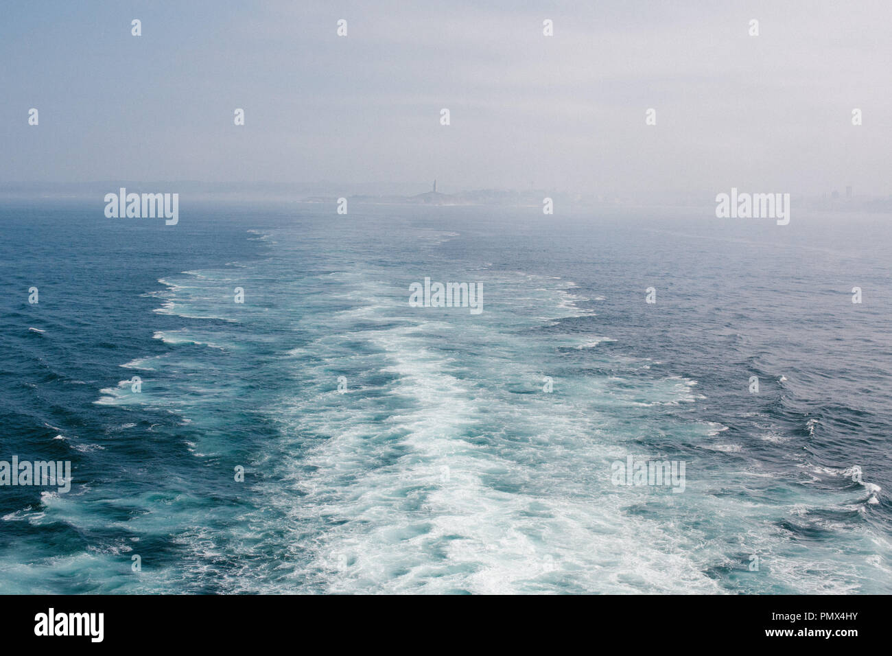 The wake behind a large cruise ship as it leaves port into open water (sea, ocean) with the distant land in the background - Stock Image