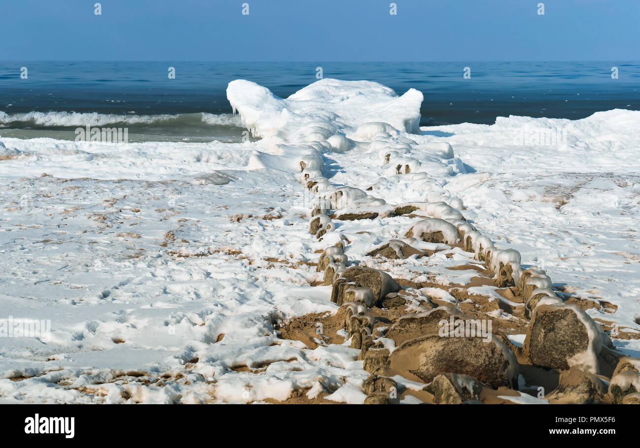 breakwaters in the ice, the ice on the breakwater in the sea - Stock Image