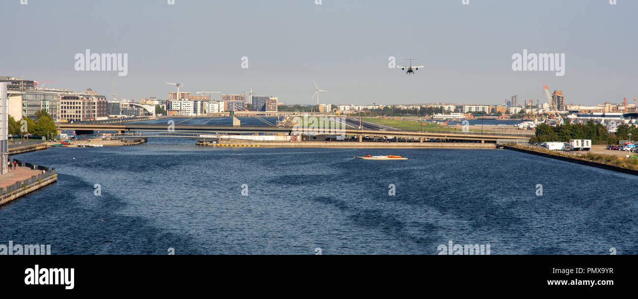 London, England, UK - September 2, 2018: A small passenger airplane flys low over Royal Victoria Dock on the approach to London City Airport in Dockla - Stock Image
