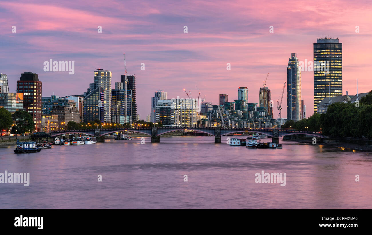 London, England, UK - September 10, 2018: The sun sets behind the River Thames and Lambeth Bridge, with the modern riverside skyline of office blocks, - Stock Image