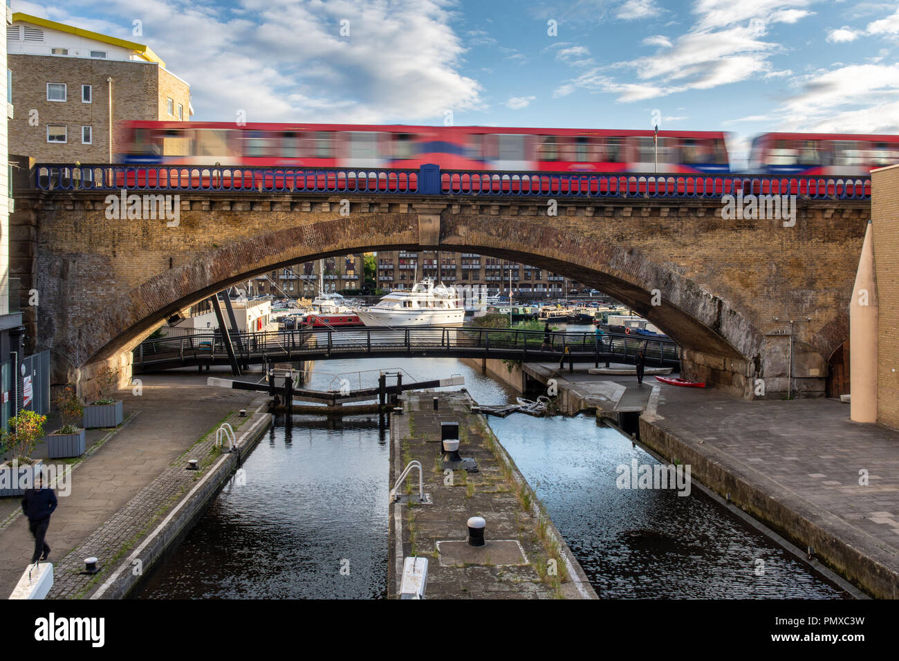 London, England, UK - September 14, 2018: A Docklands Light Railway train forms a blur as it speeds across a viaduct over the Regent's Canal at Limeho - Stock Image