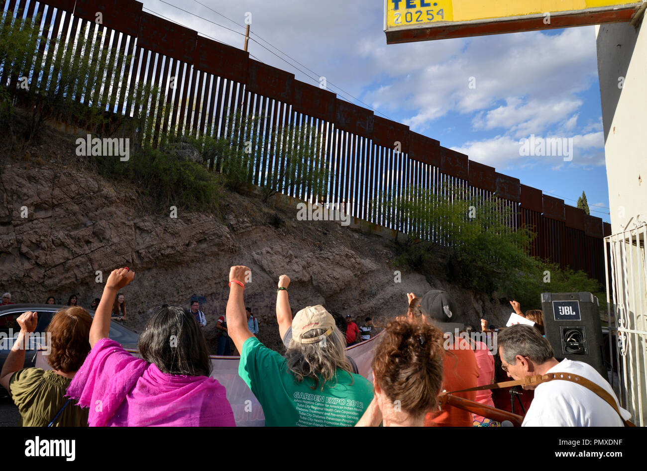 Protestors in Nogales, Sonora, Mexico, raise their fists to the border wall in Nogales, Arizona, USA, during a protest of the shooting of a teen in Me - Stock Image