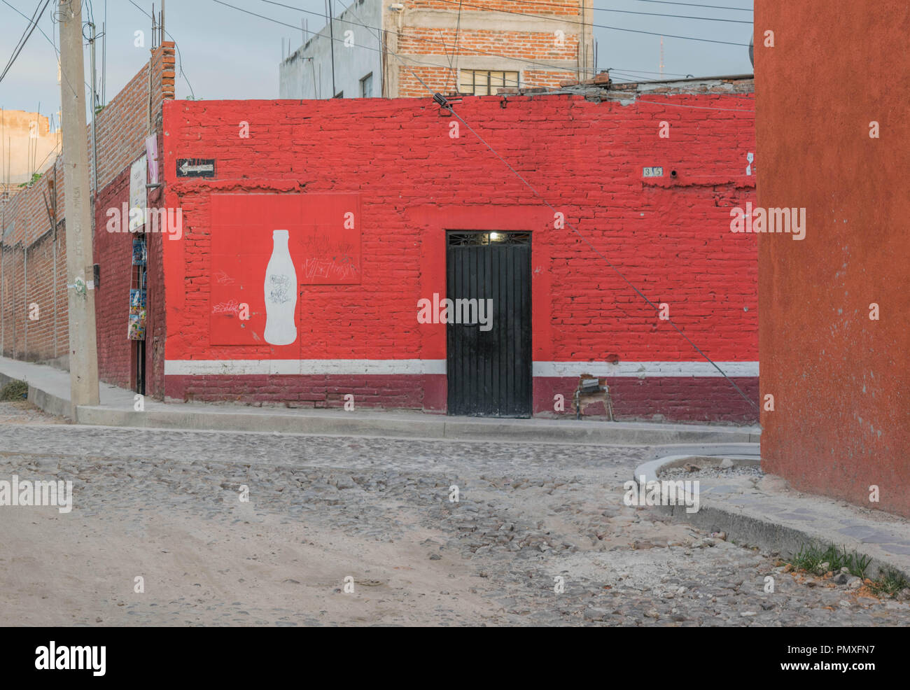 A store front with a red wall and a cola bottle painting in white, and a cobblestone street. On a street corner in San Miguel de Allende, Mexico. Stock Photo