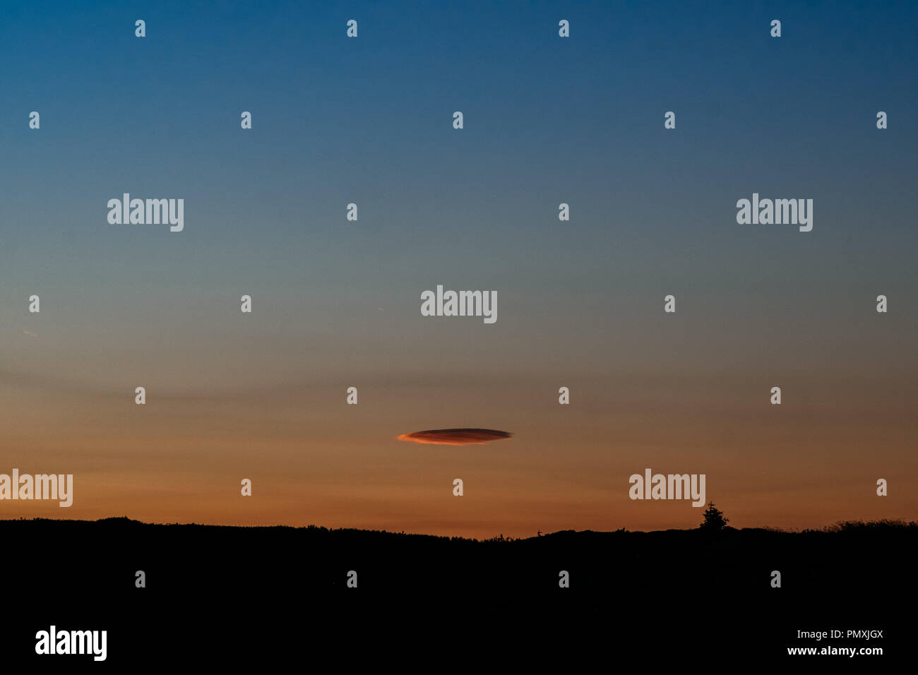 Single stratus cloud in the sky at sunset Stock Photo