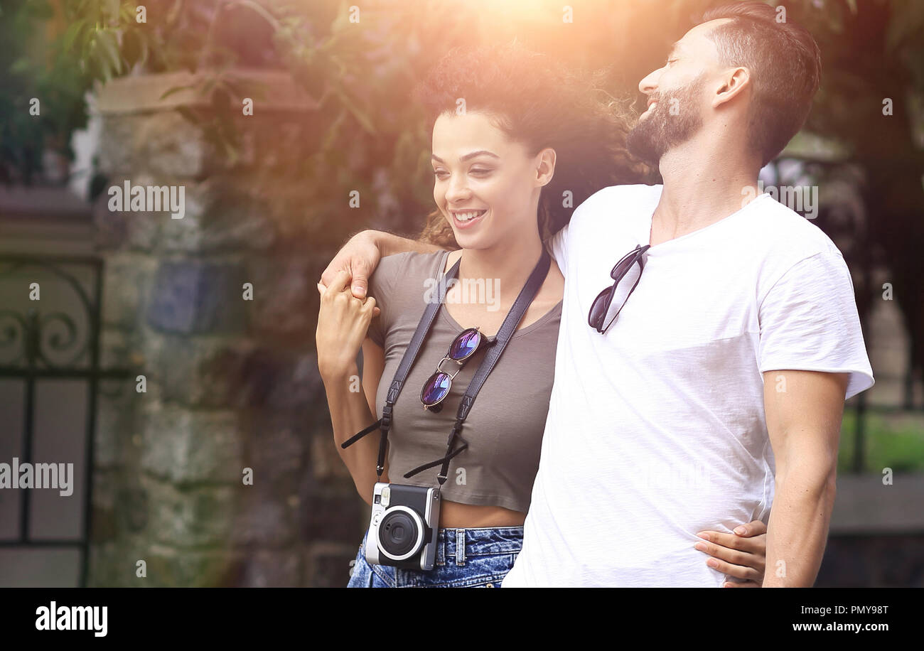 Cheerful young couple walking on urban street - Stock Image