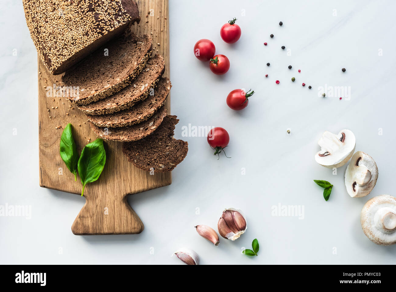 flat lay with cut bread on wooden cutting board, black pepper and vegetables for cooking breakfast on white marble surface Stock Photo