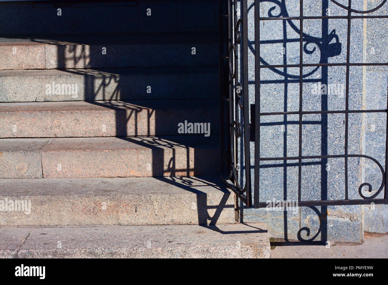 Excellent granite staircase with the openwork cast-iron and the staircase wall - Stock Image