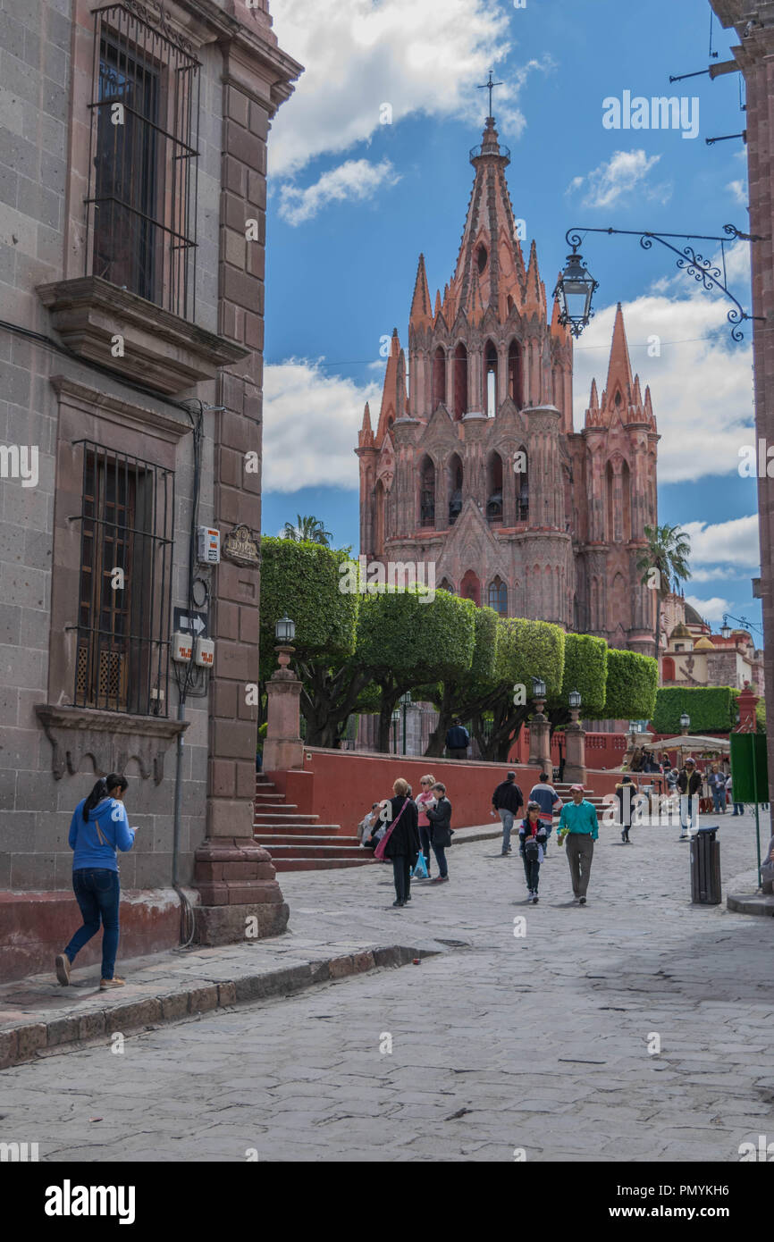 San Miguel de Allende, Mexico-October 26, 2017: Parroquia de San Miguel Arcangel, towering over the El Jardin, a cloudy blue sky, and people walking - Stock Image