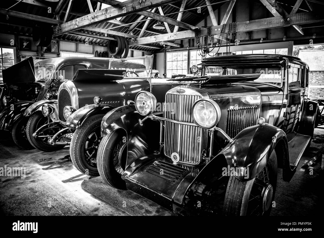 Detailed Arty Black And White Landscape Close Up Of Shiny Polished Vintage Classic Cars Parked Side By Side On Display In An Open Garage Space Stock Photo Alamy