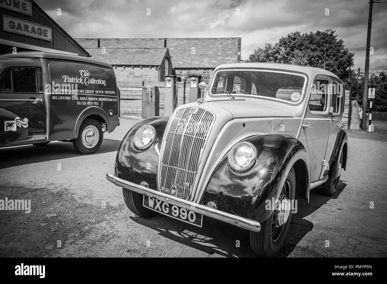 Arty, black and white, landscape shot of vintage vehicles parked outside vintage garage. Vintage petrol pumps in background. - Stock Image