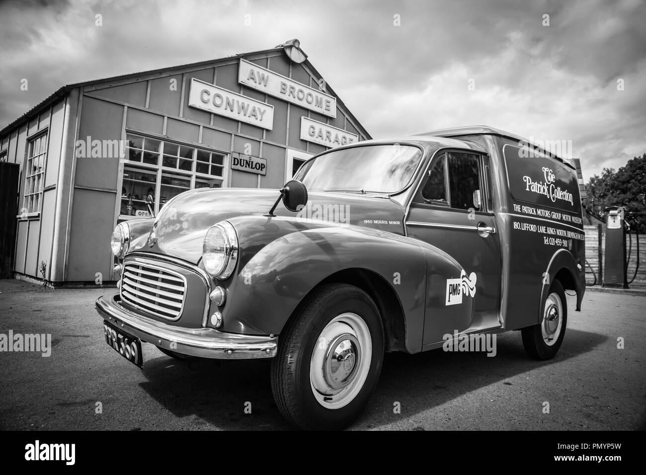 Arty, black and white, landscape shot of vintage vehicle parked outside vintage garage. - Stock Image