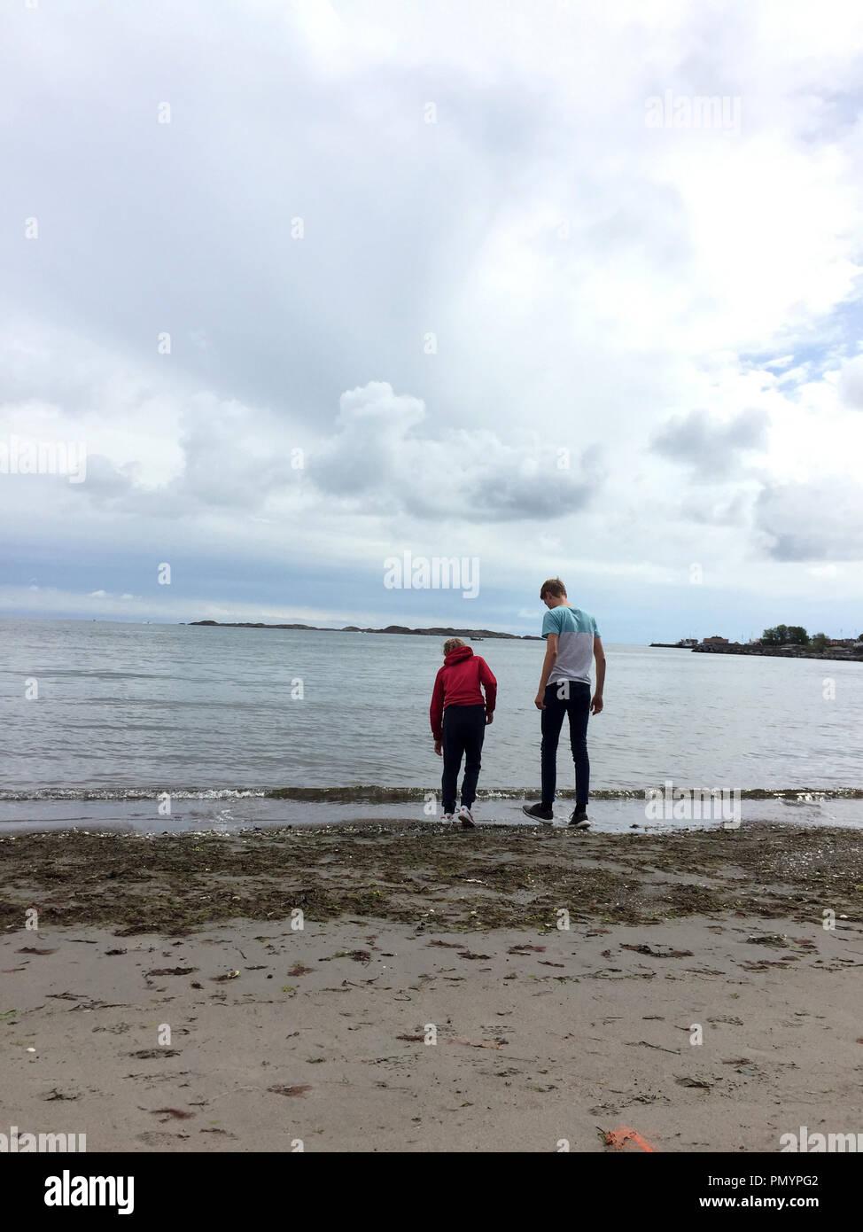 389ceadc40c1 a boy and a girl on a beach on a cloudy summer day