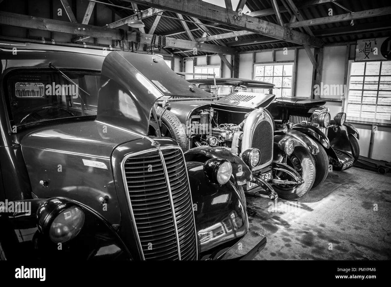 Detailed, arty, black and white, landscape close up of shiny, polished vintage classic cars parked, side by side, in an open garage space. - Stock Image
