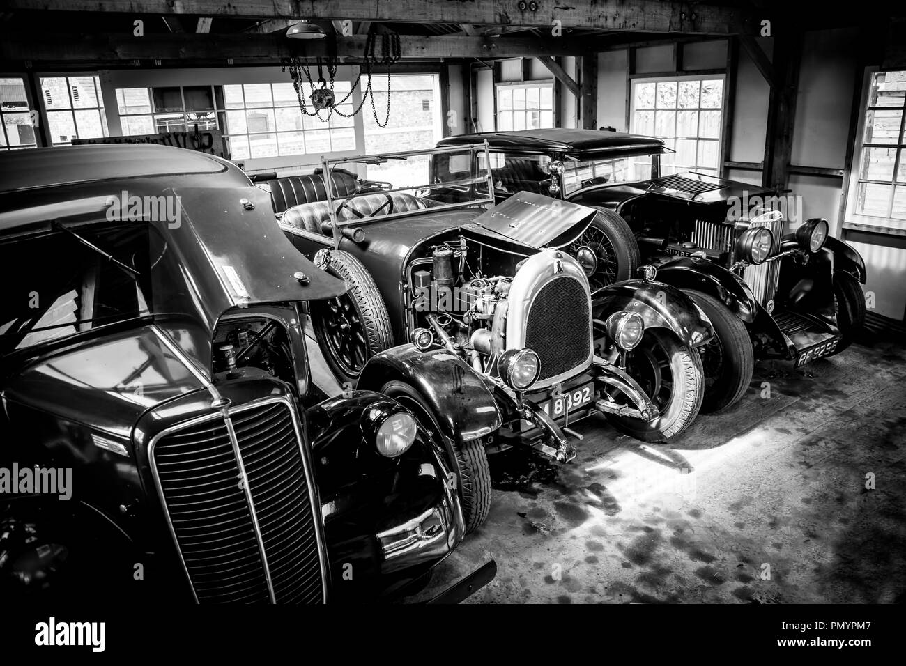 Arty, black and white, landscape shot of classic cars parked, side by side, in a garage taken from a high angle. - Stock Image