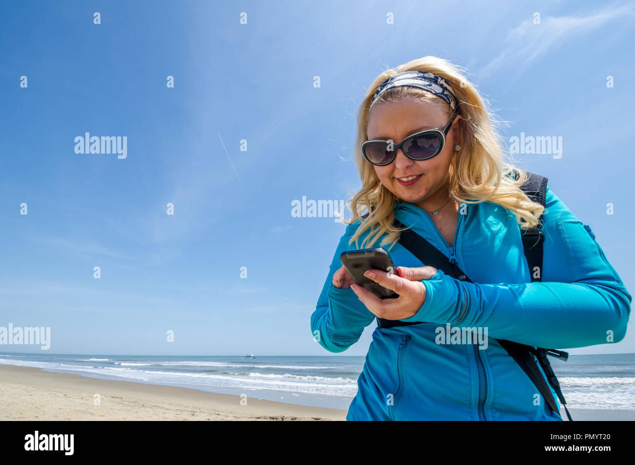 Blonde woman uses smartphone while on the beach at the ocean - Stock Image