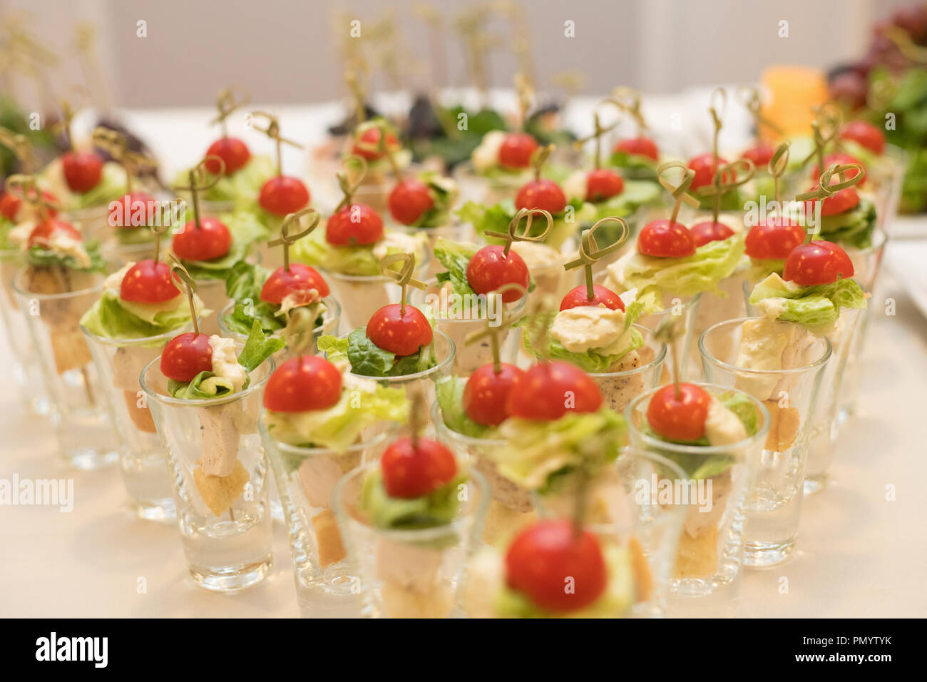 Triangular rows of cocktails with vegetables on the banquet table - Stock Image