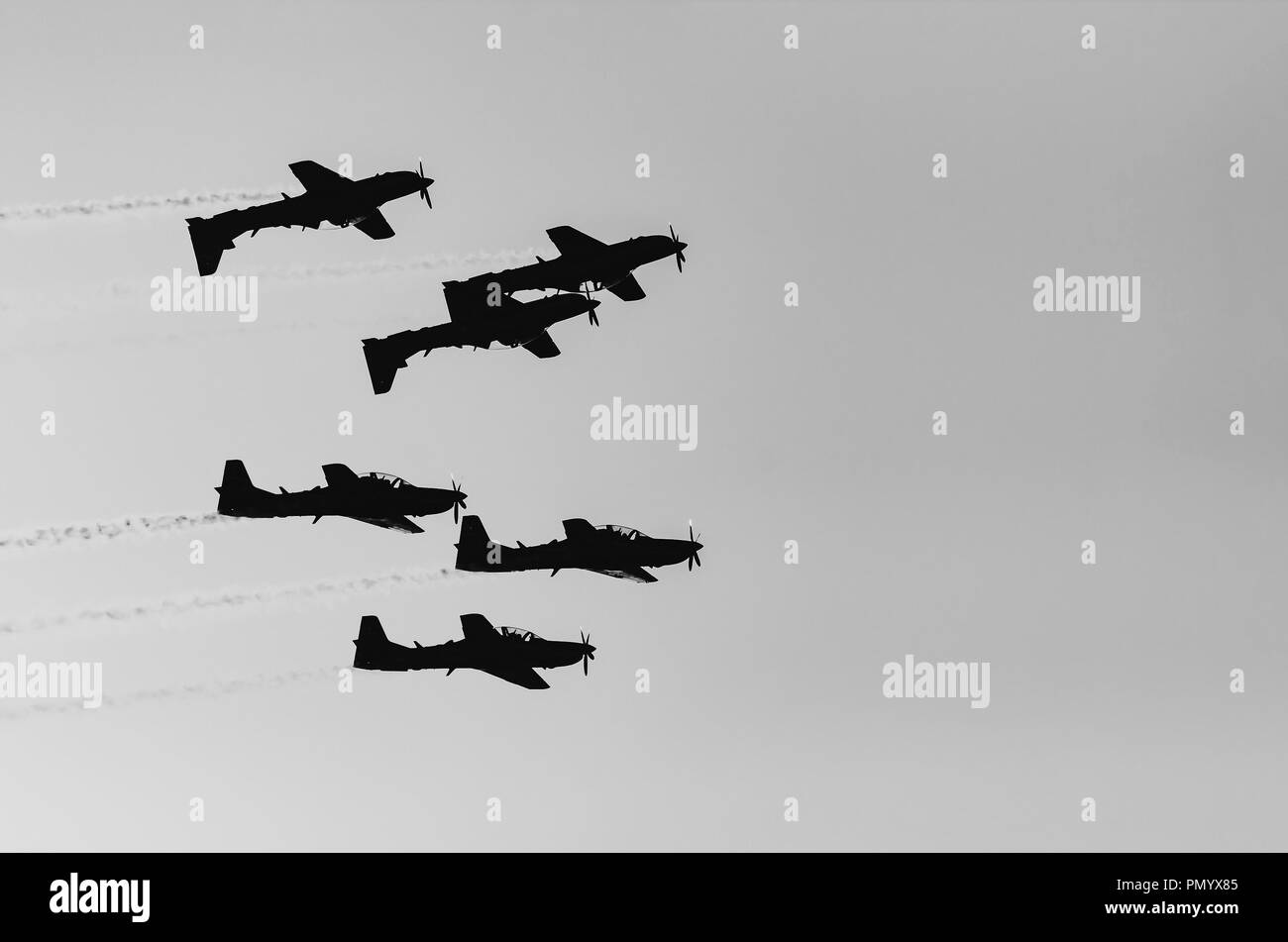 Three planes flying upside down and others three flying normally under. Squad flying together, smoke trail behind. Planes making aerial acrobatics. - Stock Image