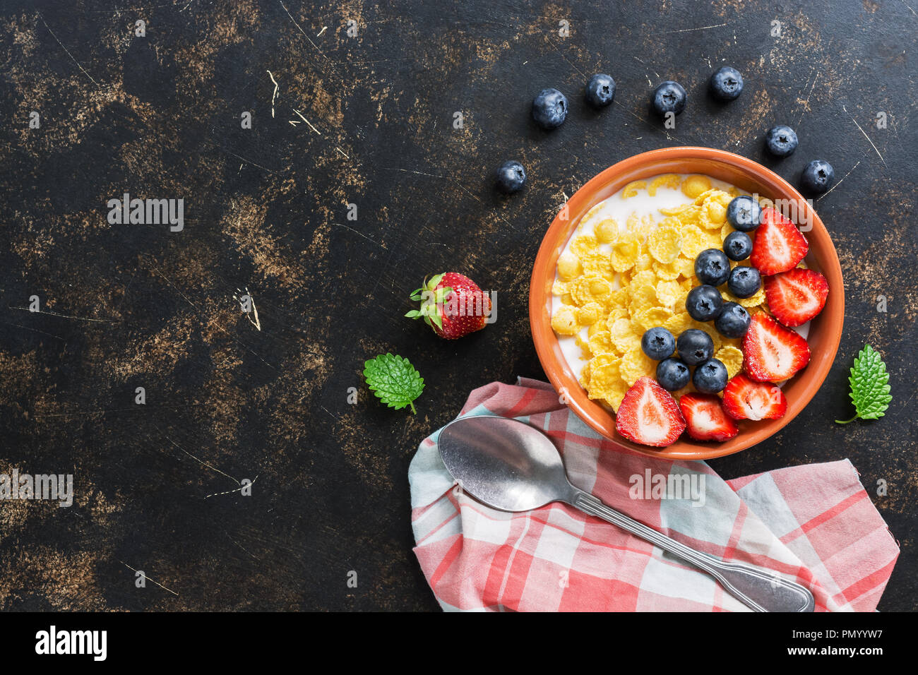Corn flakes with milk, strawberries and blueberries on a dark background. View from above, flat lay - Stock Image
