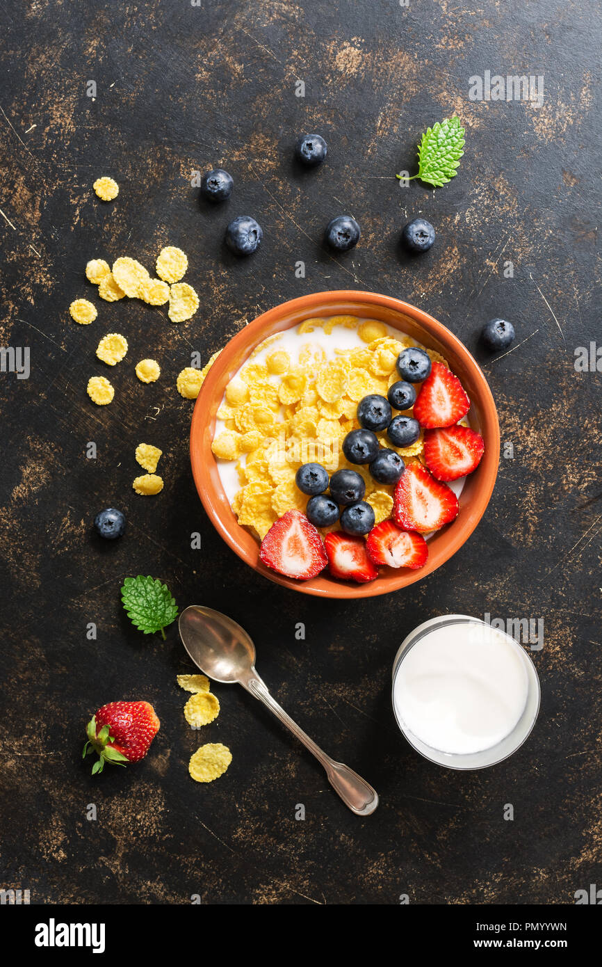 Fresh breakfast-corn flakes with milk, strawberries and blueberries on a dark background. View from above, flat lay - Stock Image