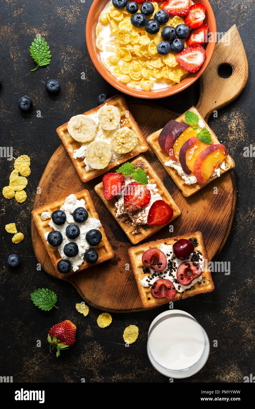Fresh breakfast - corn flakes with milk and berries, homemade waffles with fruit on a dark background. The view from above, flat lay - Stock Image