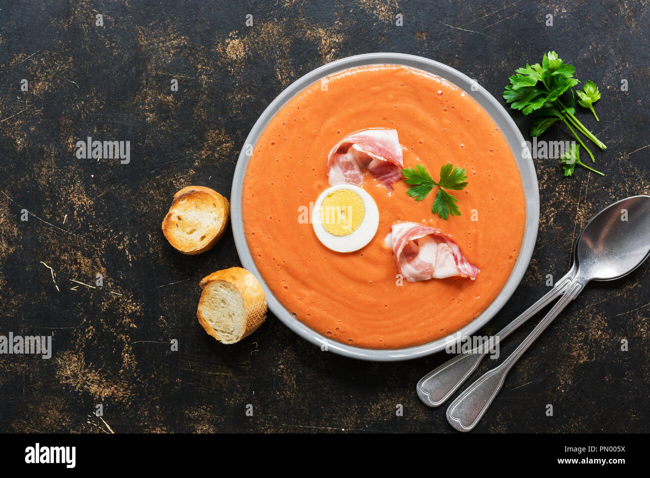 Traditional spanish andalusian tomato cream soup salmorejo served in a gray plate with ham and egg Stock Photo