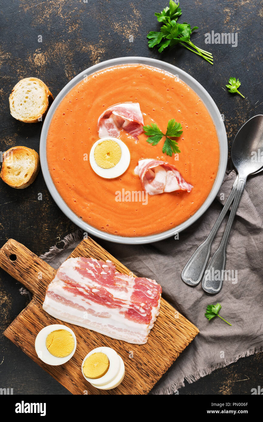 Spanish tomato soup Salmorejo served in a gray plate with ham and egg. Top view, copy space Stock Photo