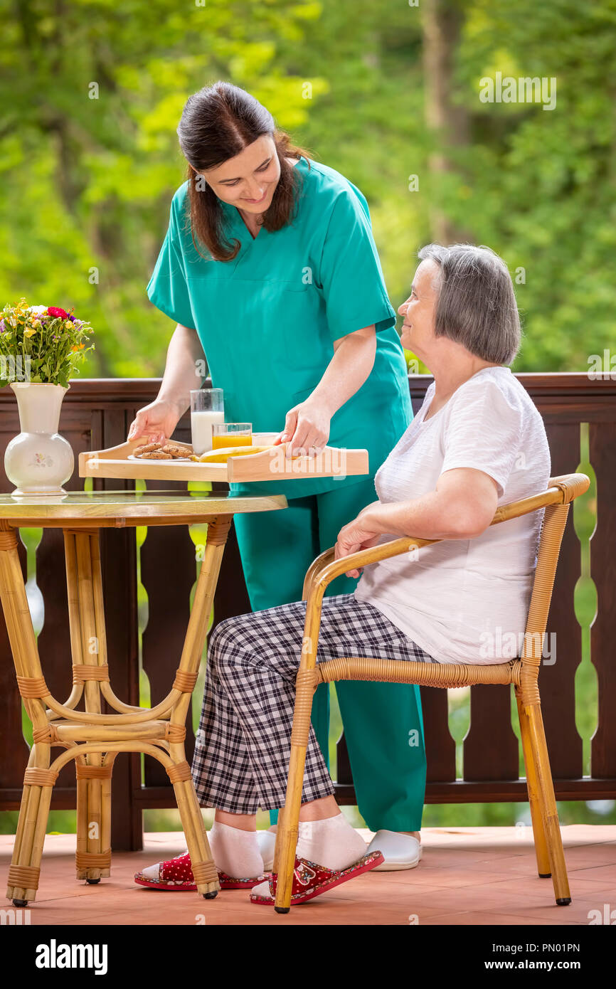 Happy nurse or caregiver serving healthy breakfast to elderly woman on the terrace at nursing home. - Stock Image