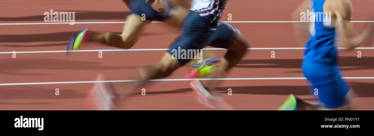 blurred motion group runners sprinters running on track stadium - Stock Image