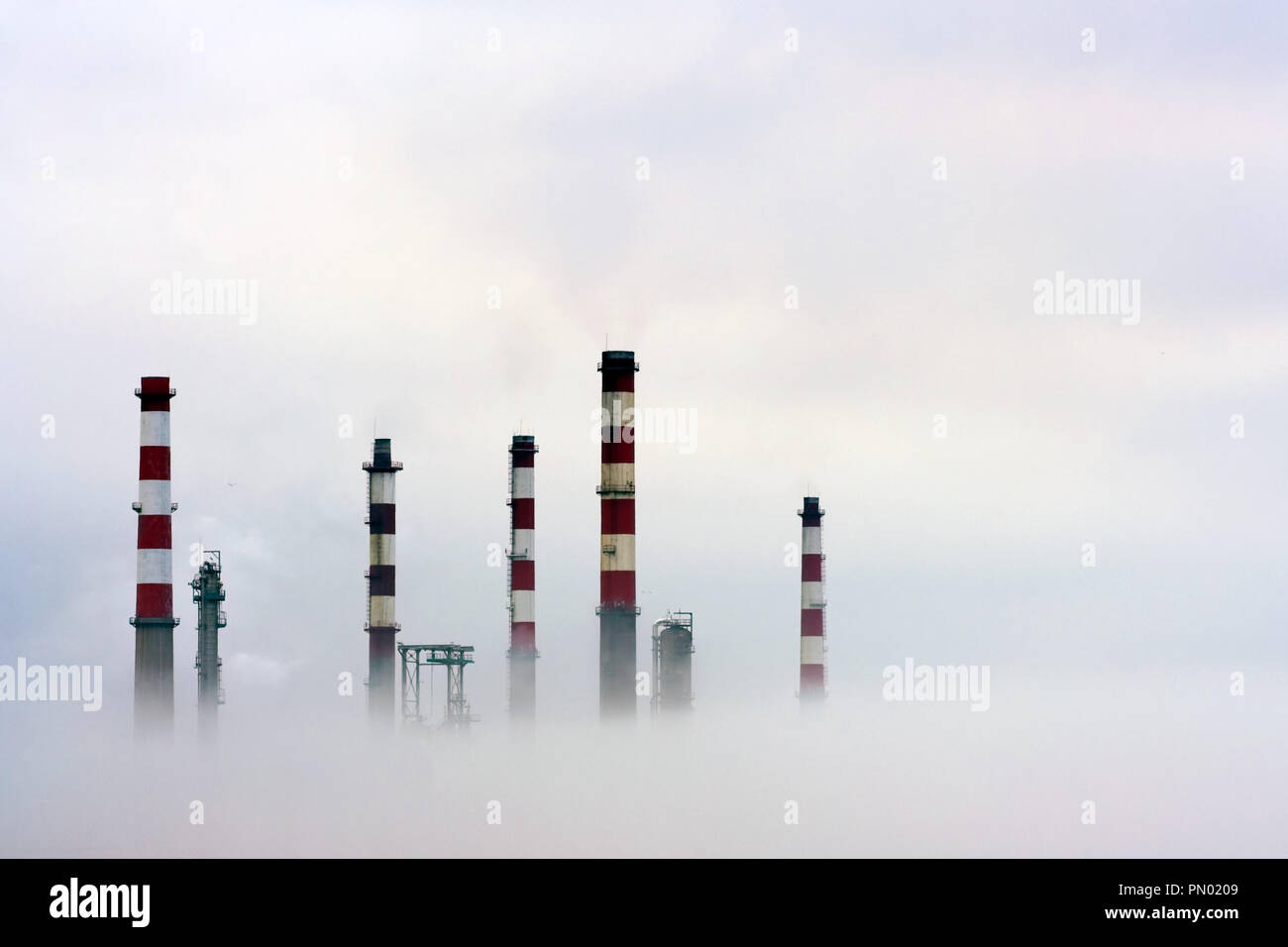 Chimneys of an oil refinery semi losted in the fog - Stock Image
