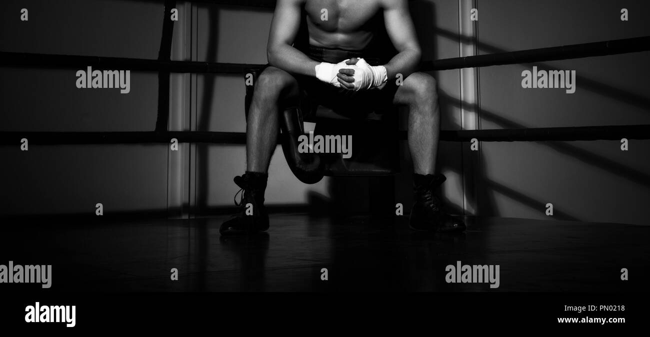 young boxer sitting on the boxing ring - Stock Image