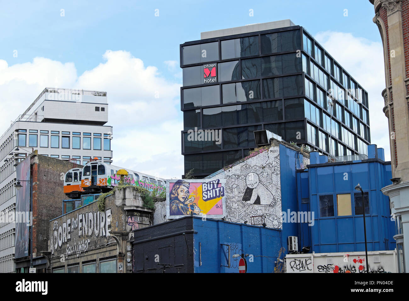 'Let's Adore and Endure Each Other' graffiti on wall with train carriages on roof Great Eastern Street art in Shoreditch East London UK  KATHY DEWITT - Stock Image