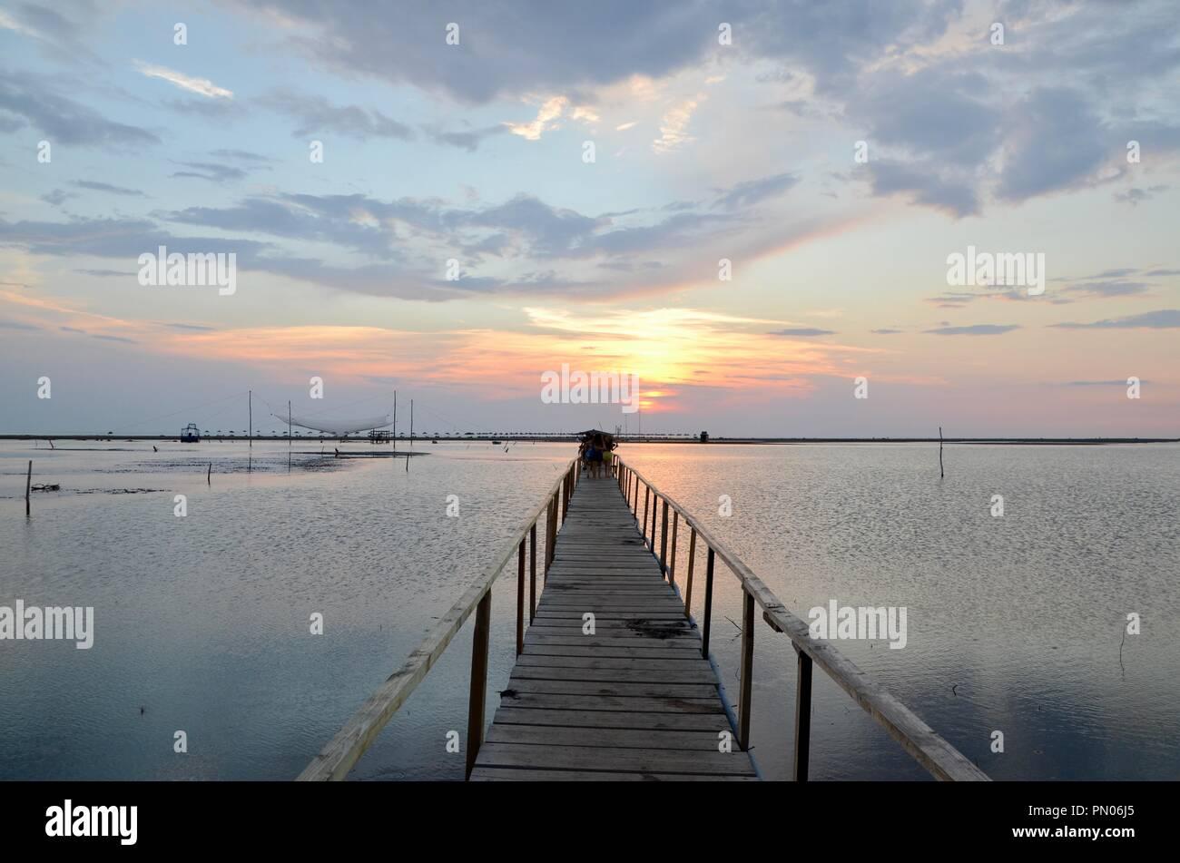 sunsetting over wooden bridge the sea in divjake resort albania - Stock Image