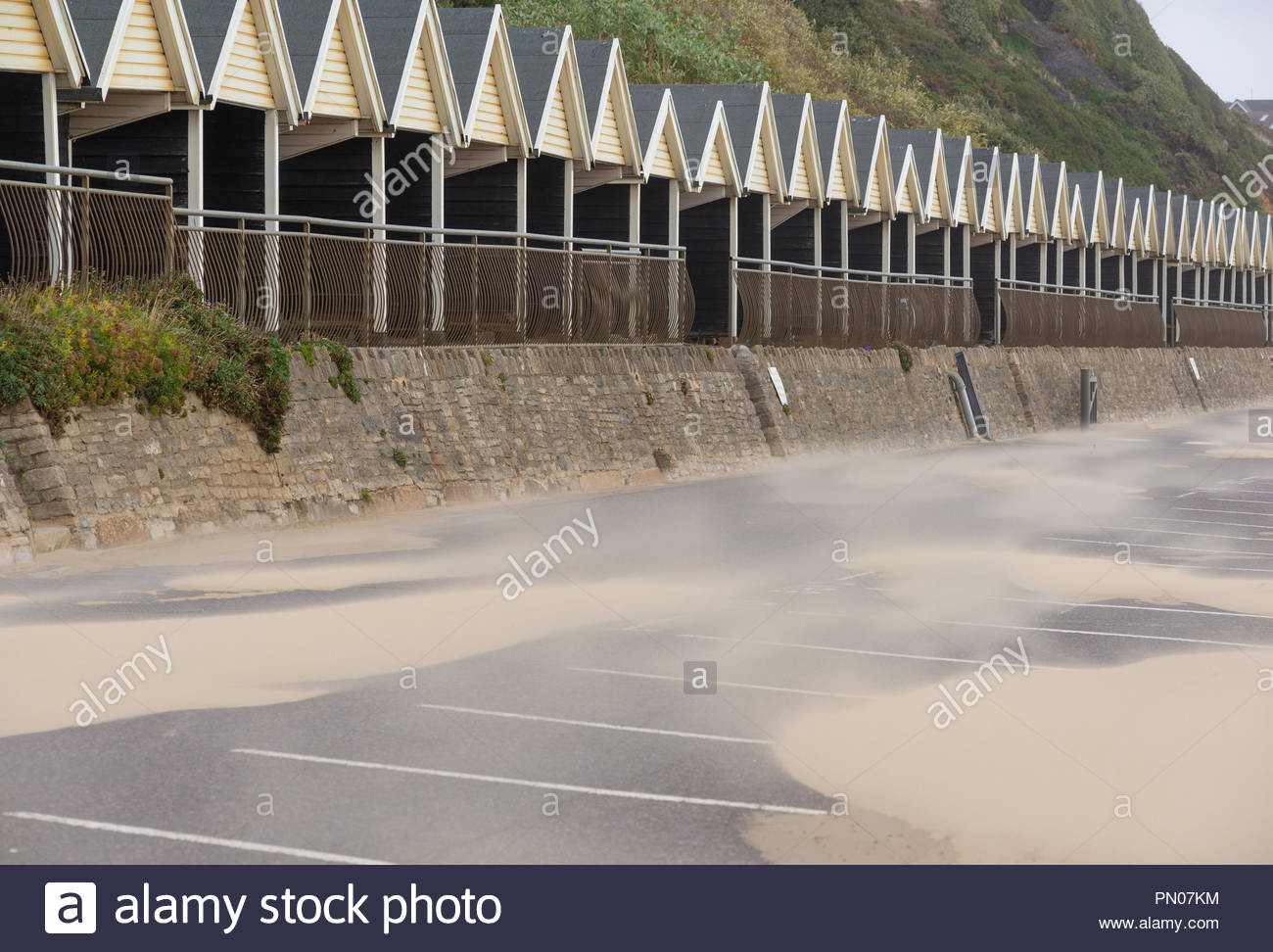 Cream sandy coloured beach huts match the colour of the sand blown onto the promenade car park at Boscombe, Bournemouth, Dorset, UK - Stock Image
