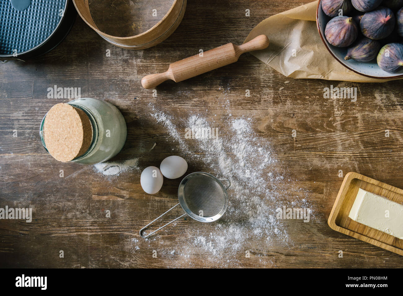 top view of messy wooden table with spilled flour and baking ingredients Stock Photo