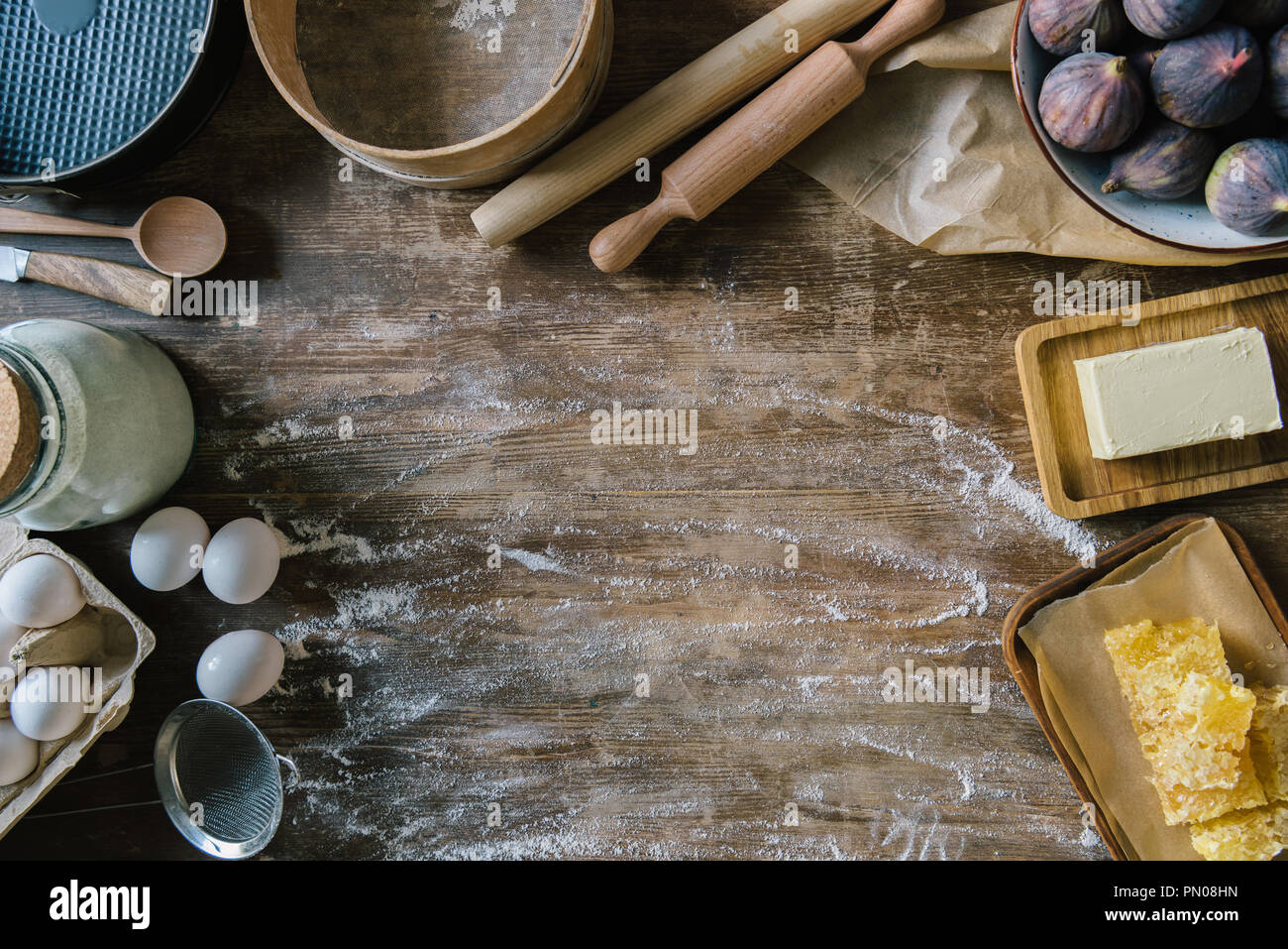 top view of messy wooden table with spilled flour and baking ingredients - Stock Image