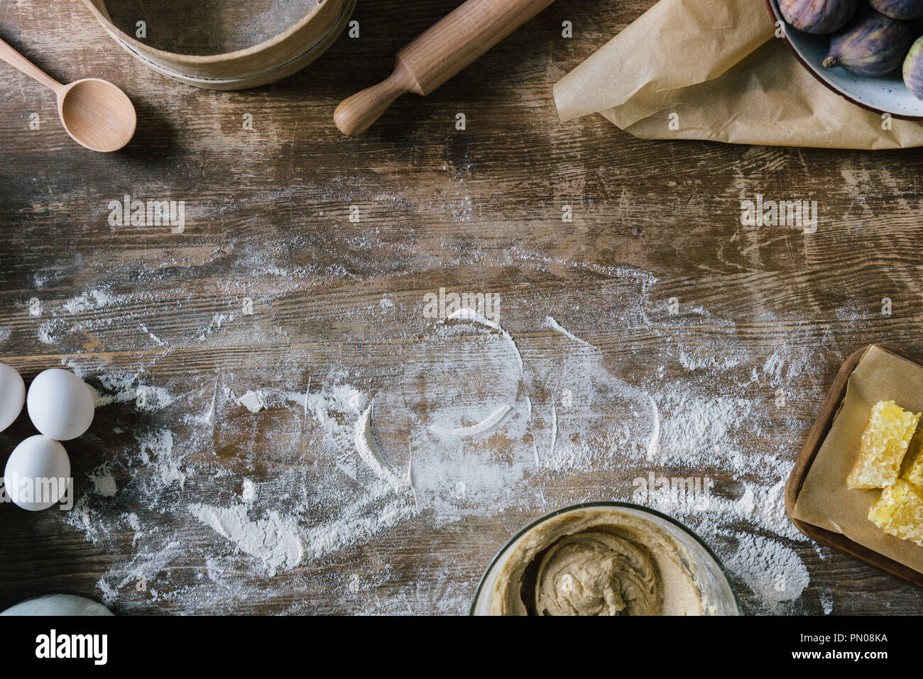 top view of messy rustic wooden table with spilled flour and baking ingredients - Stock Image