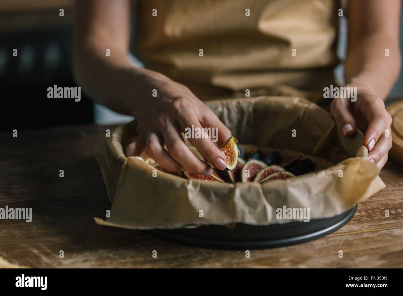 cropped shot of woman putting sliced figs into baking tray Stock Photo