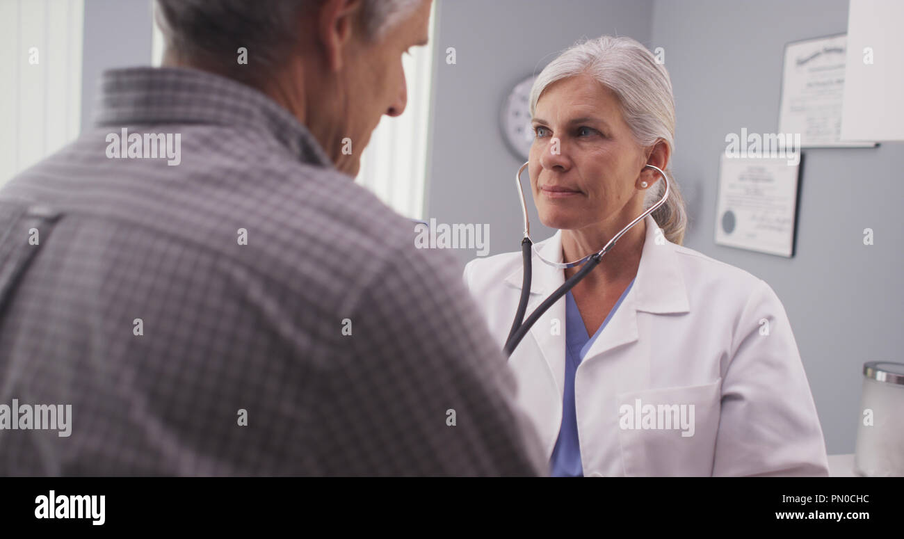 Doctor listening to patient's heart rate with stethoscope - Stock Image