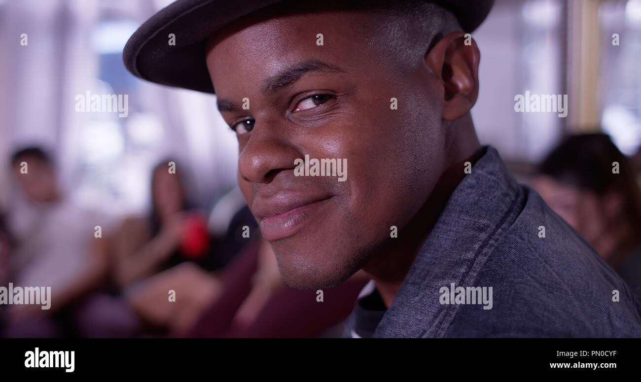 Portrait of Handsome young black hipster man smiling at camera with group of friends partying in background - Stock Image