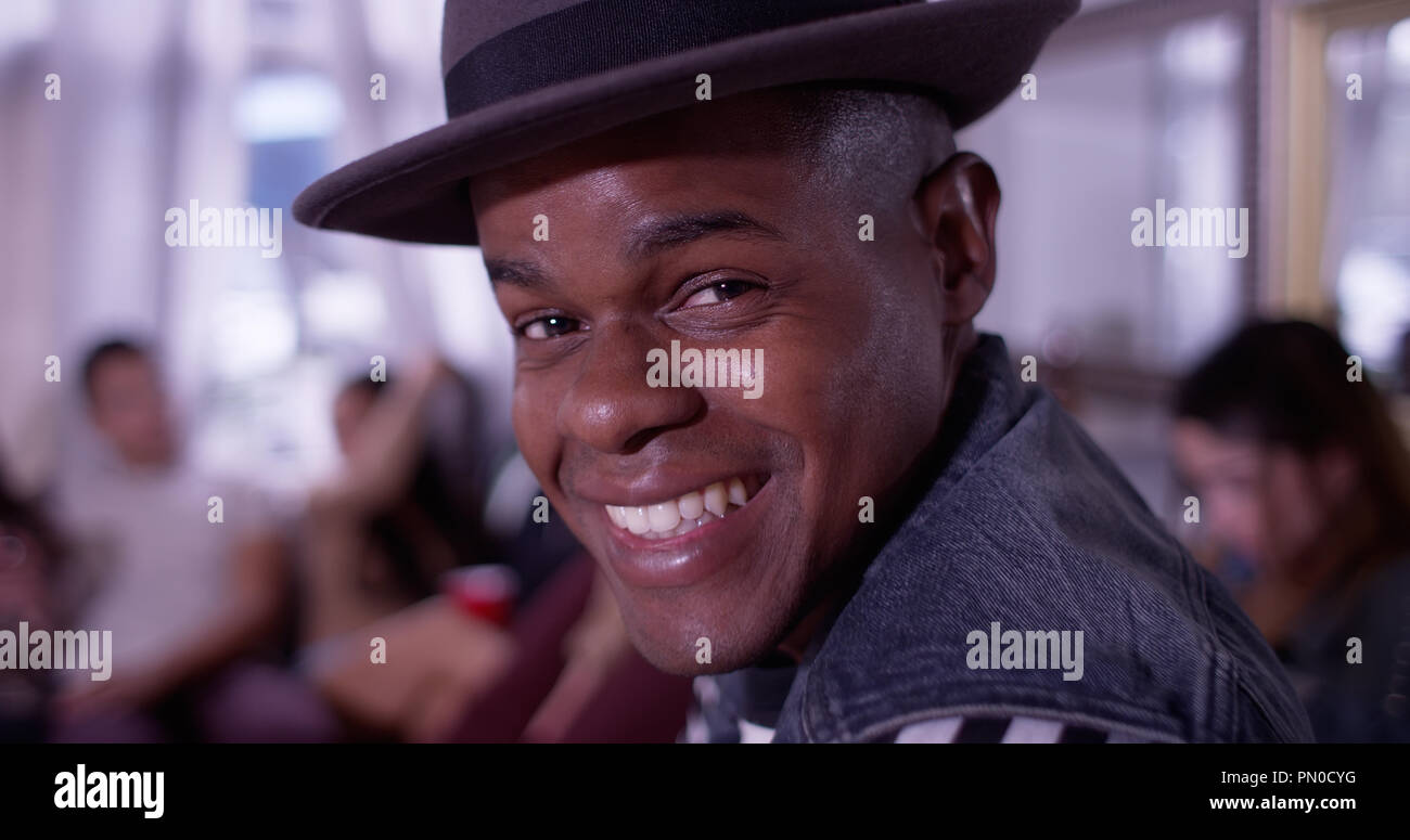 Portrait of Handsome young black hipster man smiling and laughing with group of friends partying in background - Stock Image