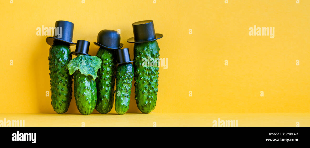 Comical green Cucumbers family on yellow background. Five funny vegetables with black old fashioned hats. Creative design food poster template. Copy space - Stock Image