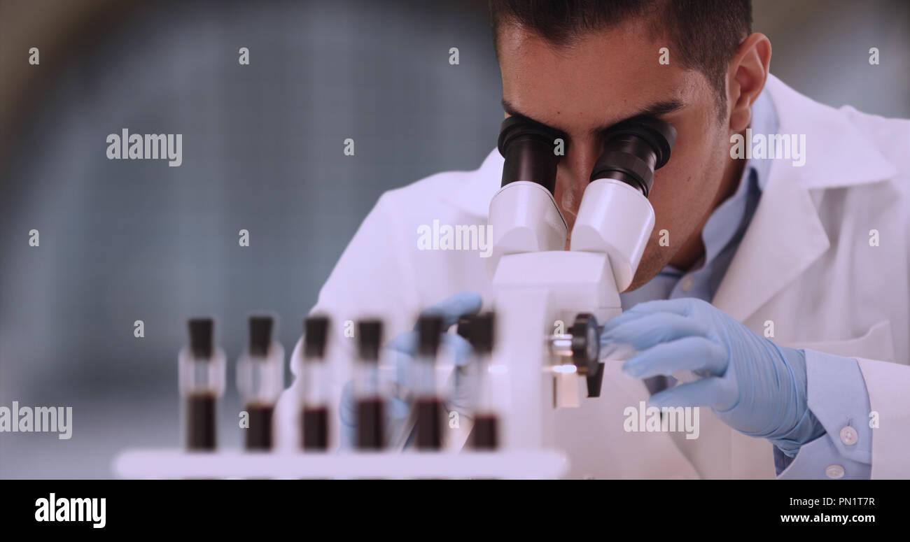 Hispanic male forensic scientist examining blood sample through microscope - Stock Image