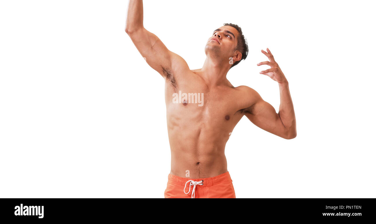 Happy Millennial Hispanic man posing in swim trunks on white background - Stock Image