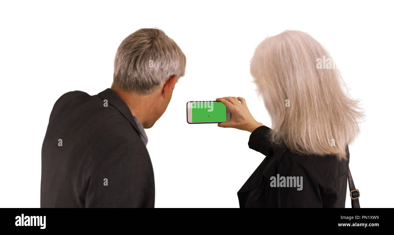 Elderly couple using smartphone to take pictures on white background - Stock Image