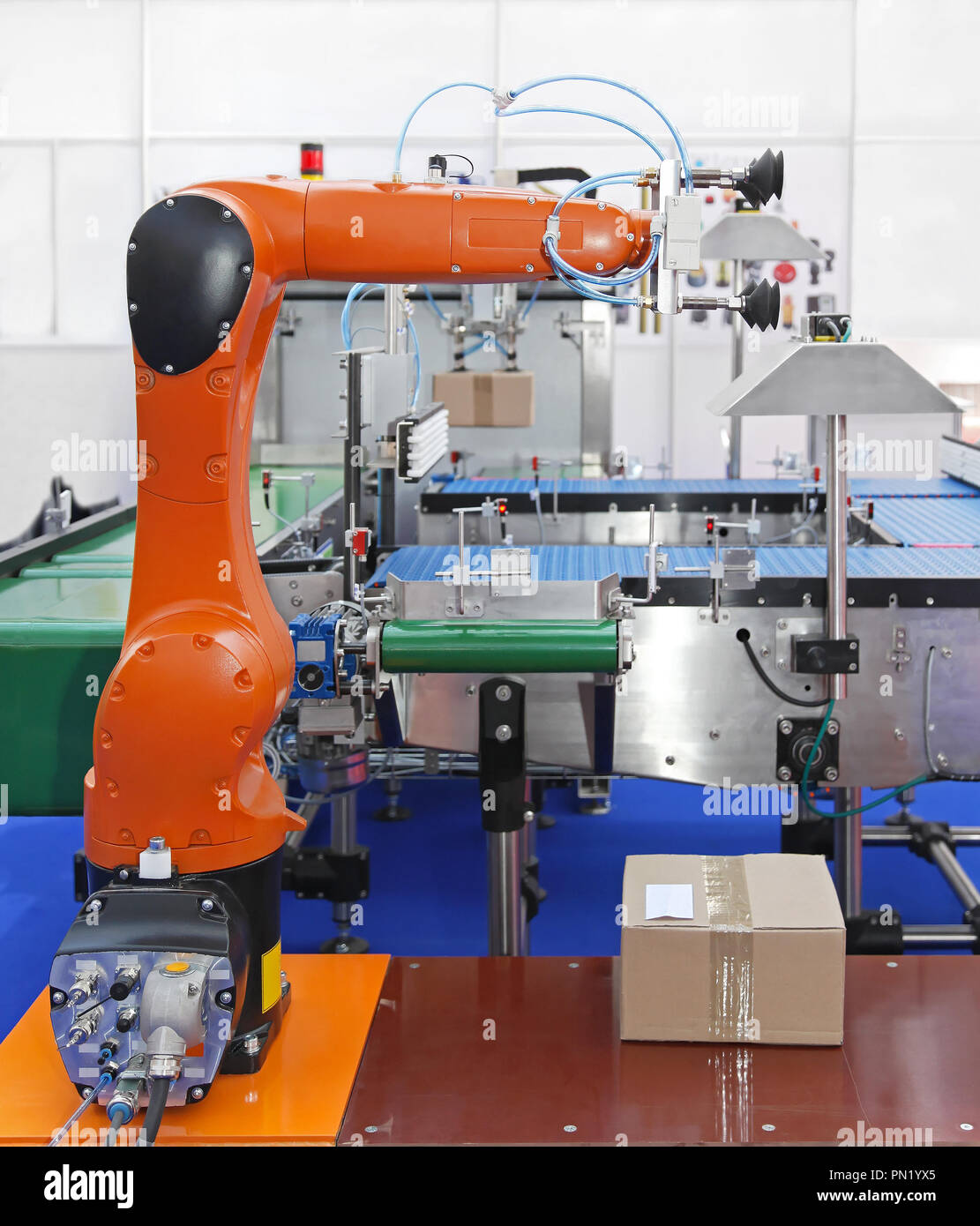 Articulated robotic arm at packaging line in factory - Stock Image